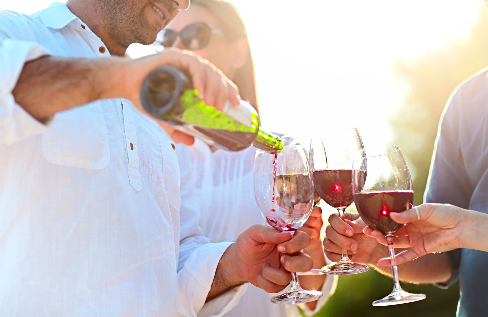 man pouring red wine in wine glasses