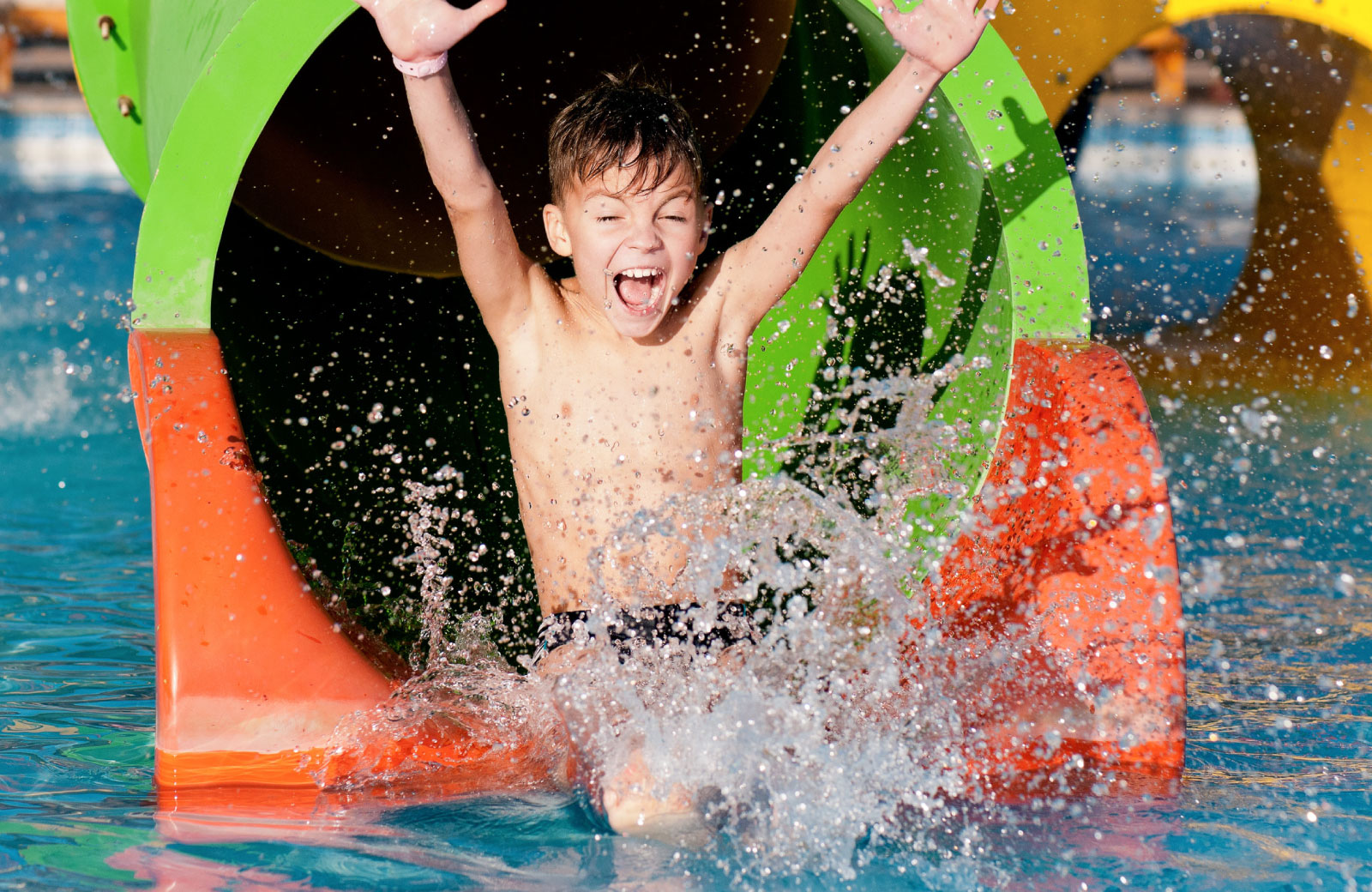 little boy enjoying in a water theme park