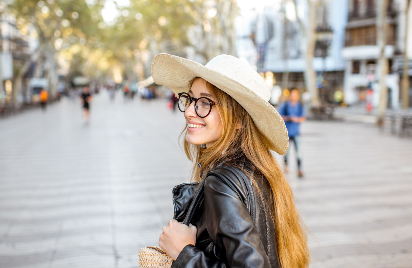 young woman with large hat and glasses exploring town