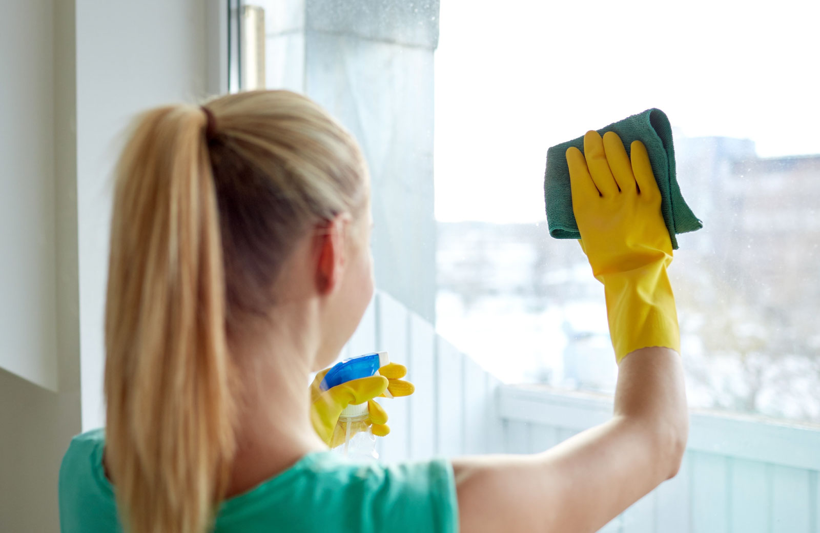 young woman with yellow gloves cleaning window