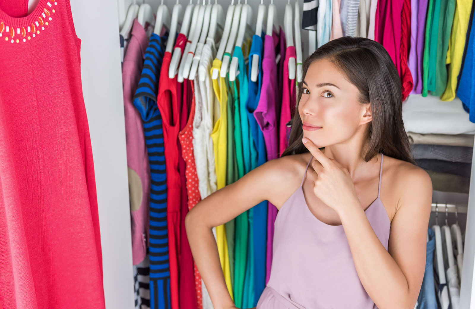 young woman in closet full of clothes thinking