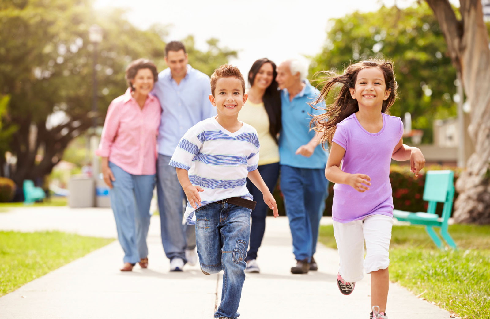 children running happily with family in background