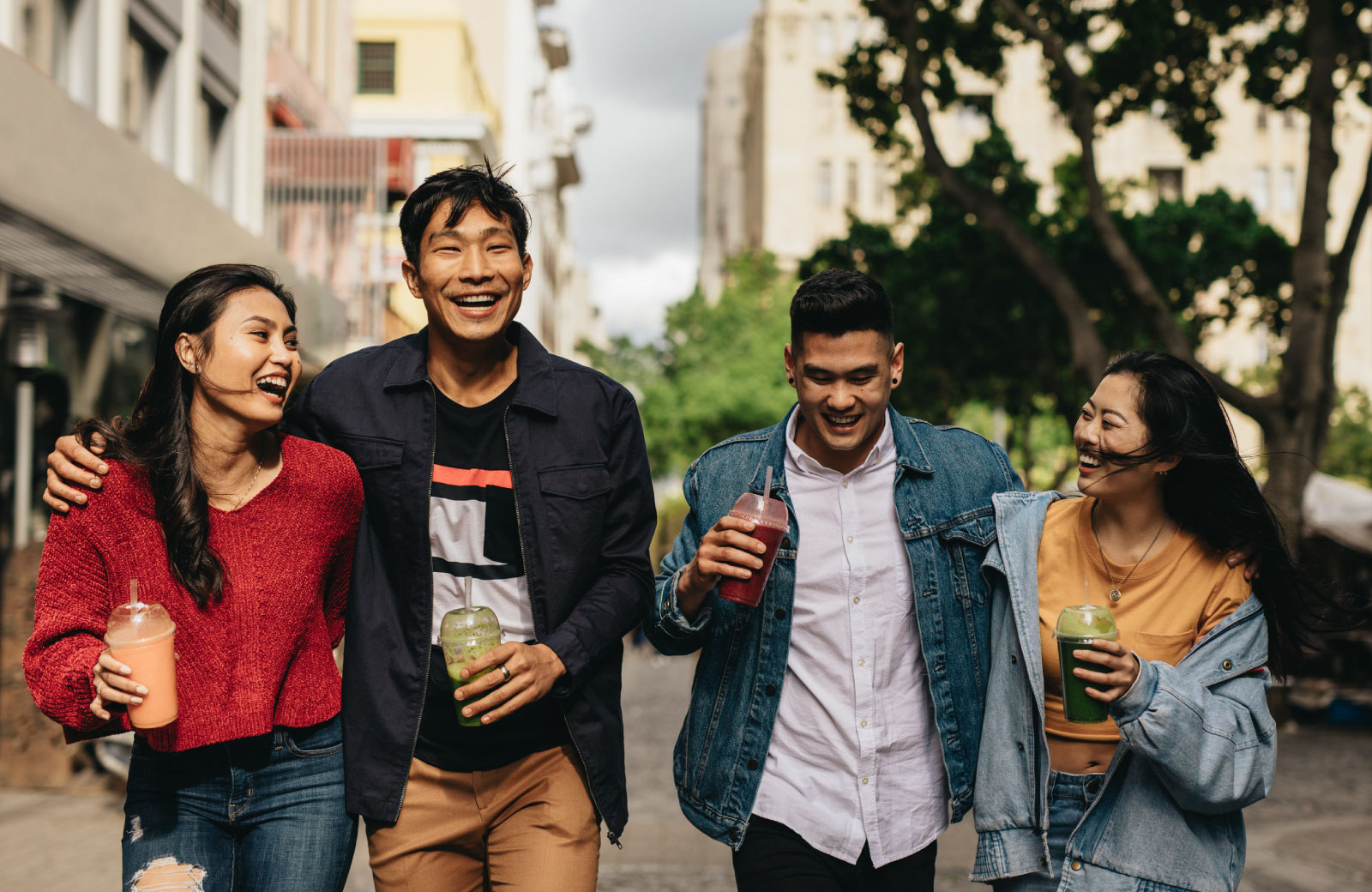 group of young Asians strolling with drinks in hand