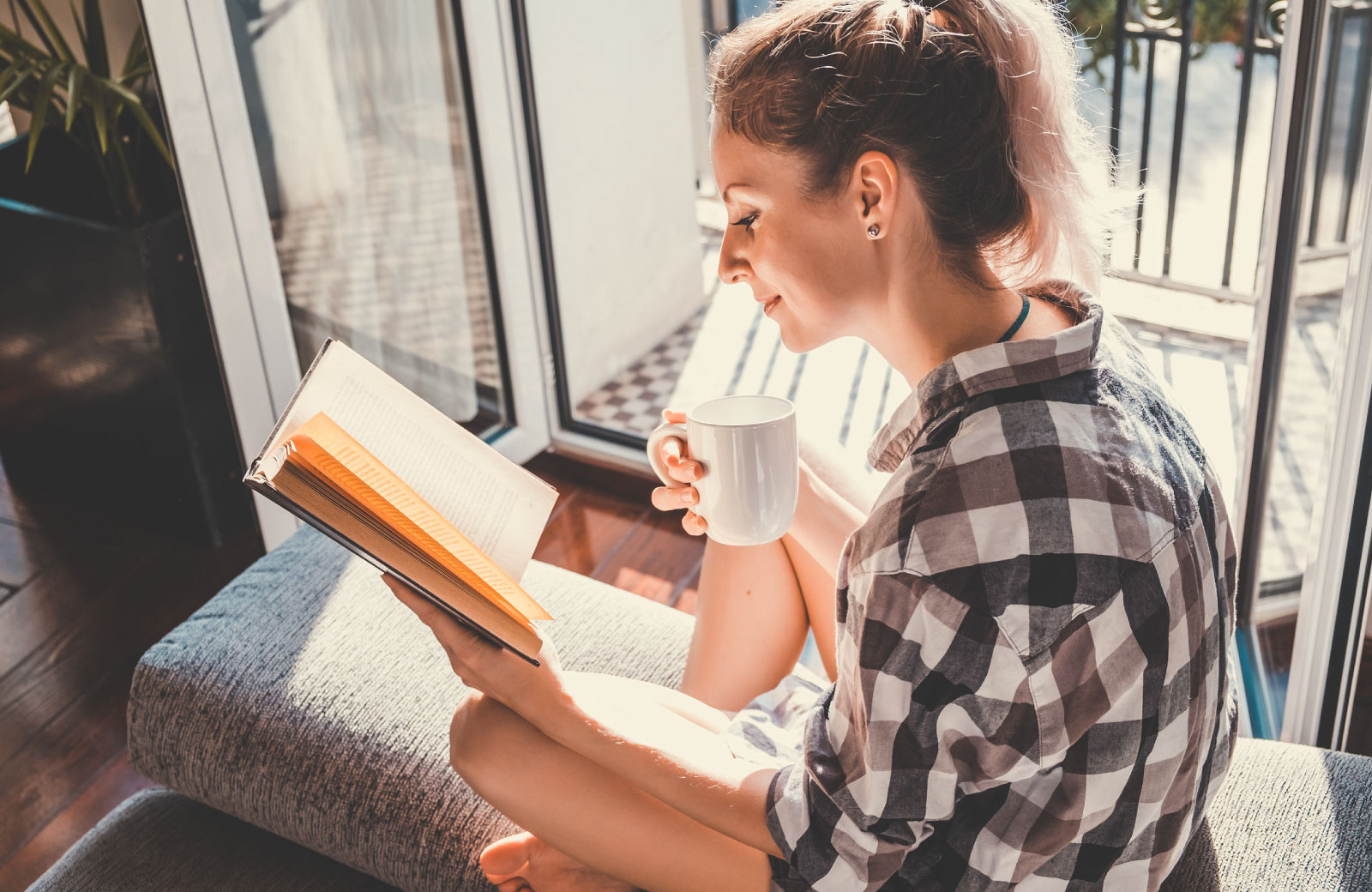 girl reading a book with mug in hand