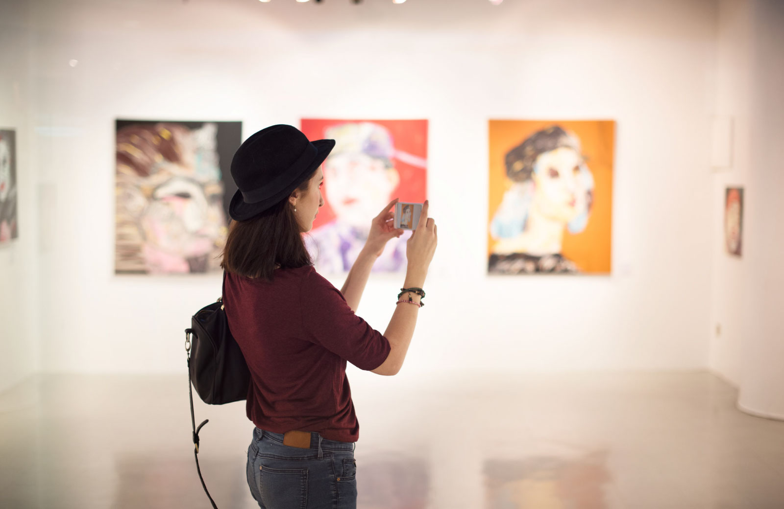 woman taking pictures in an art gallery