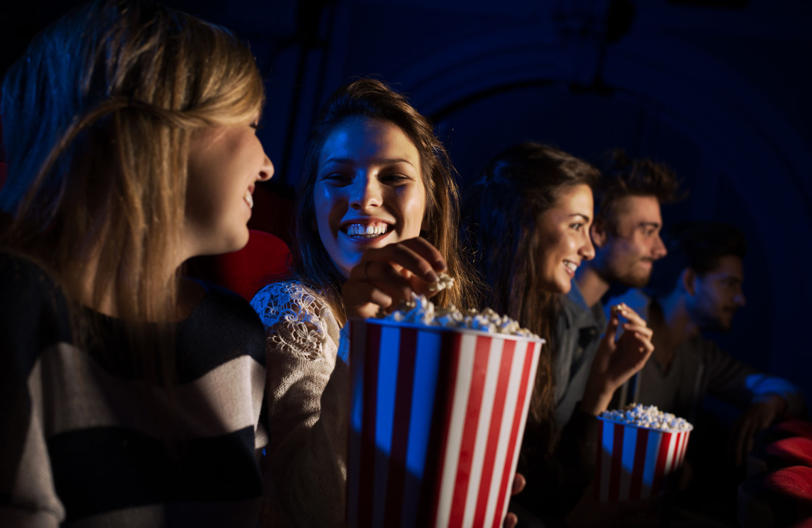 group of people watching movie in a cinema eating popcorn