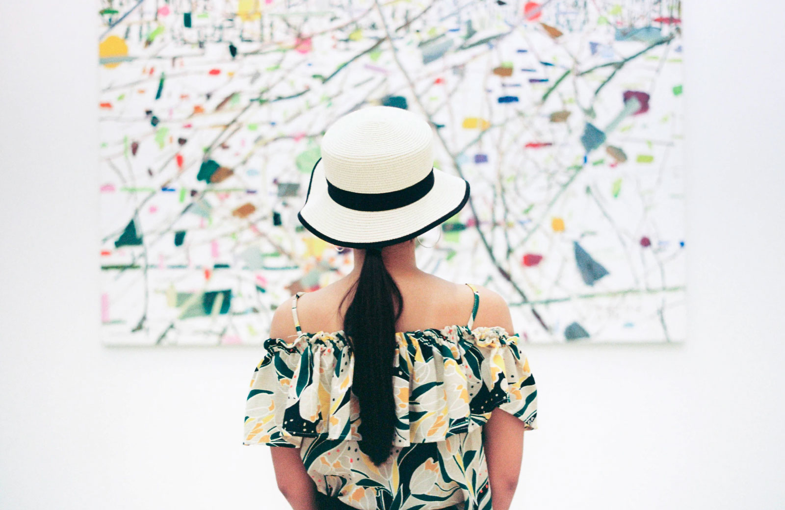 woman in a dress and hat looking at a painting