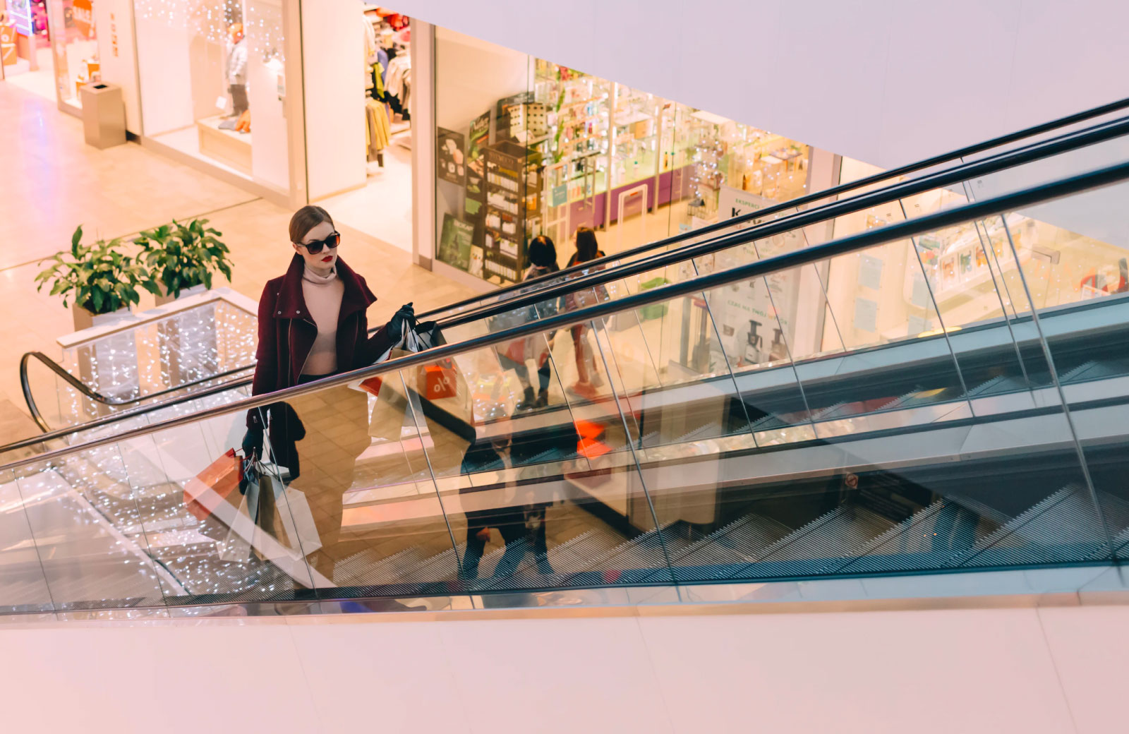 woman in jacket and shades holding shopping bags on an mall escalator