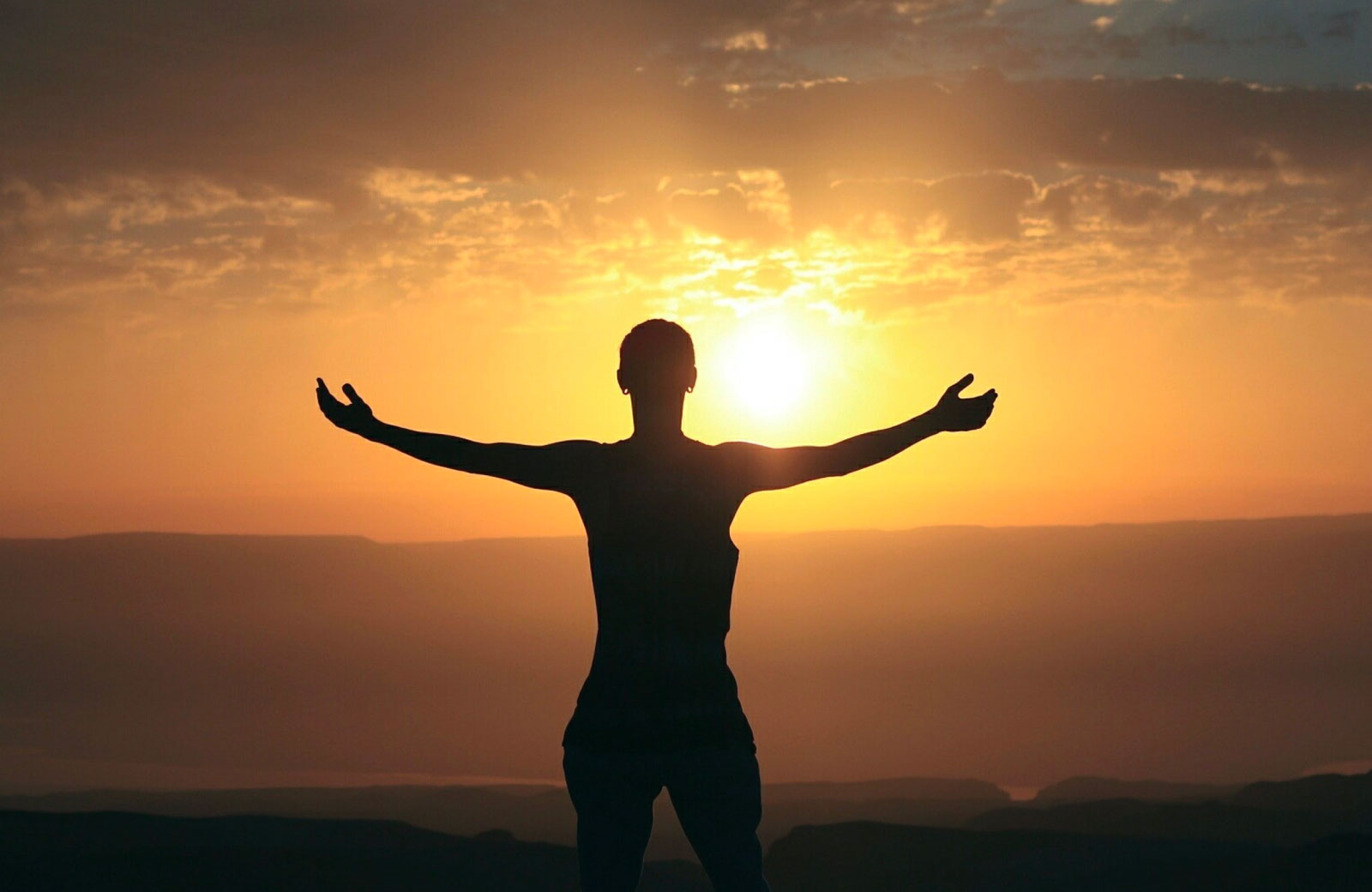 person with arms widely stretched facing the sunset