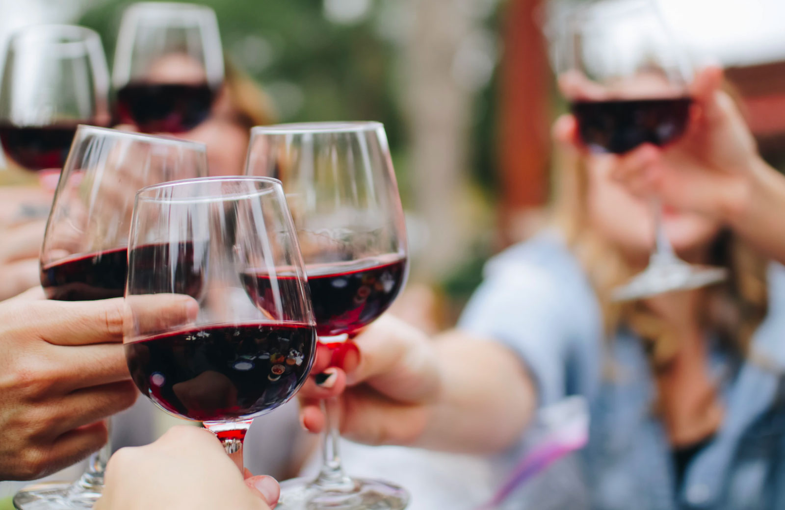 people toasting glasses with red wine