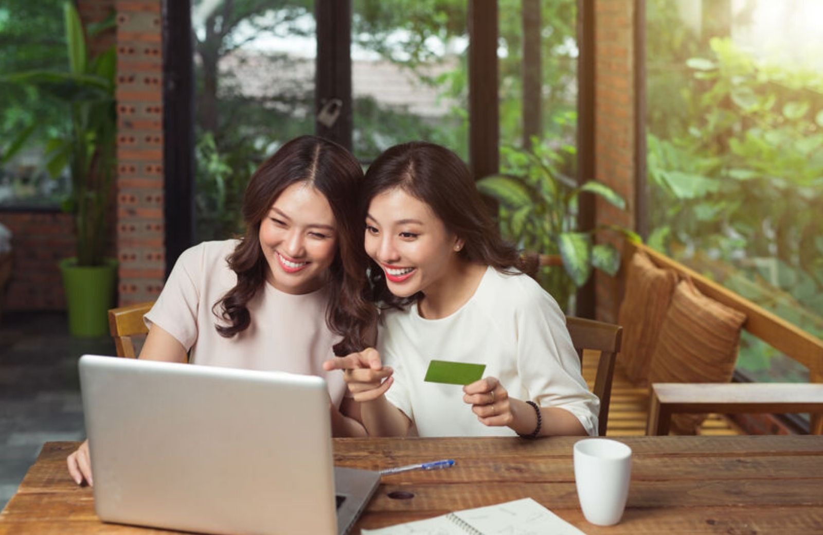 two girls shopping online holding credit card