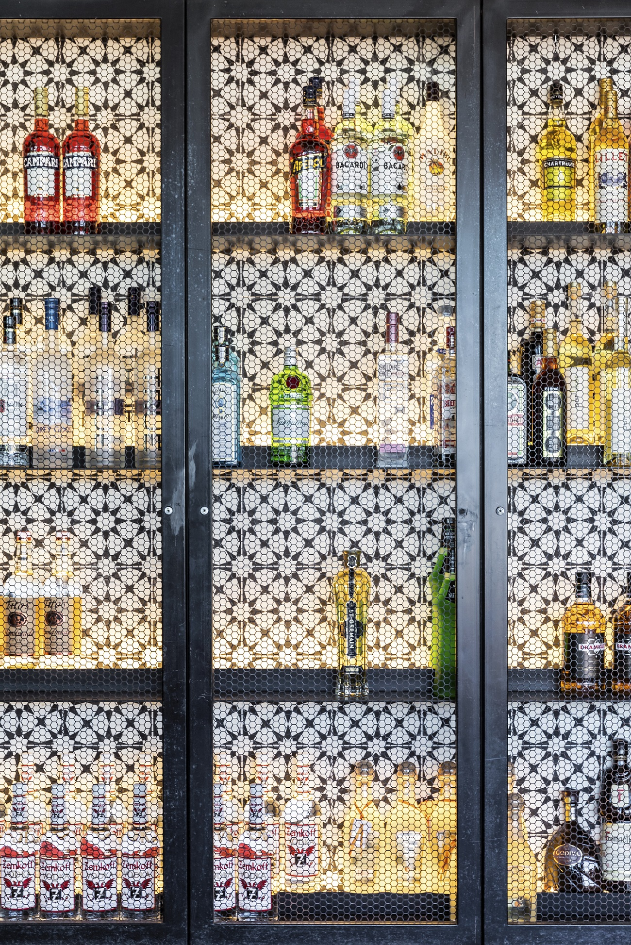 shelves of alcohol bottles behind fancy glass doors - new high rise apartments NYC