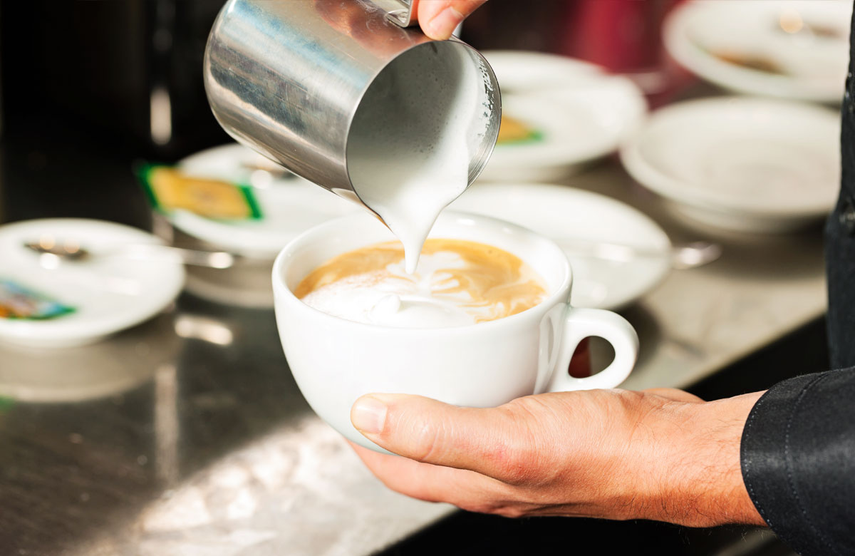 barista making a latte at a coffee shop - The Madrid Westchester LA Neighborhood
