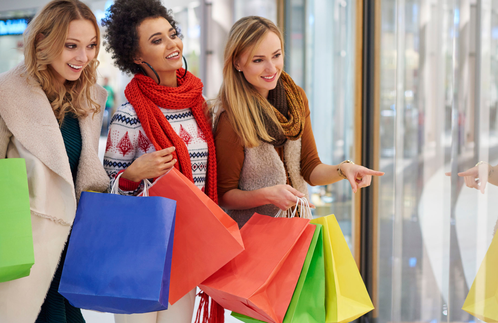 3 women shopping carrying multi colored shopping bags - Wall Street apartments