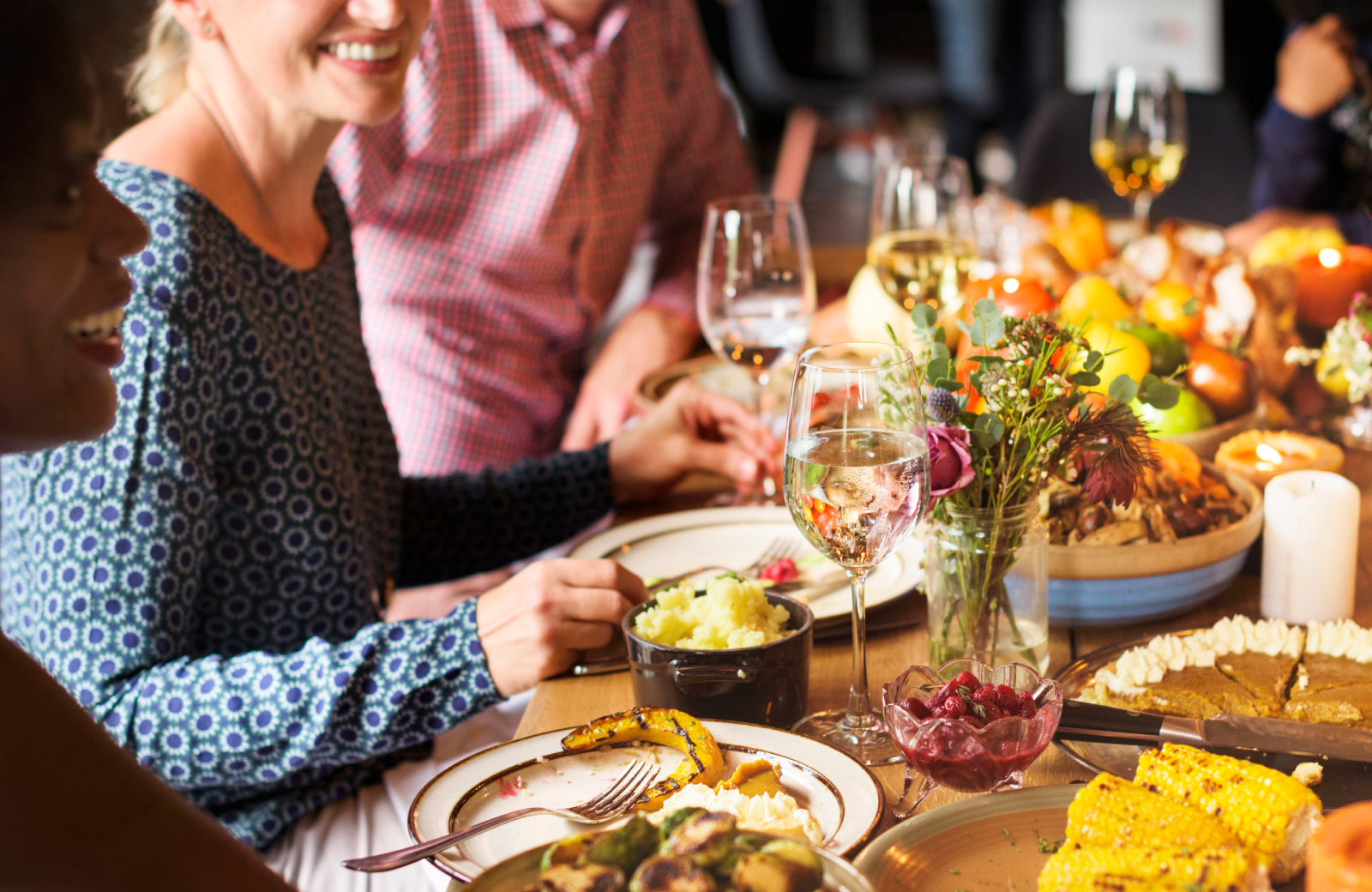 close up of friends sharing wine & thanksgiving dinner at a table - 15 Cliff Financial District luxury apartments