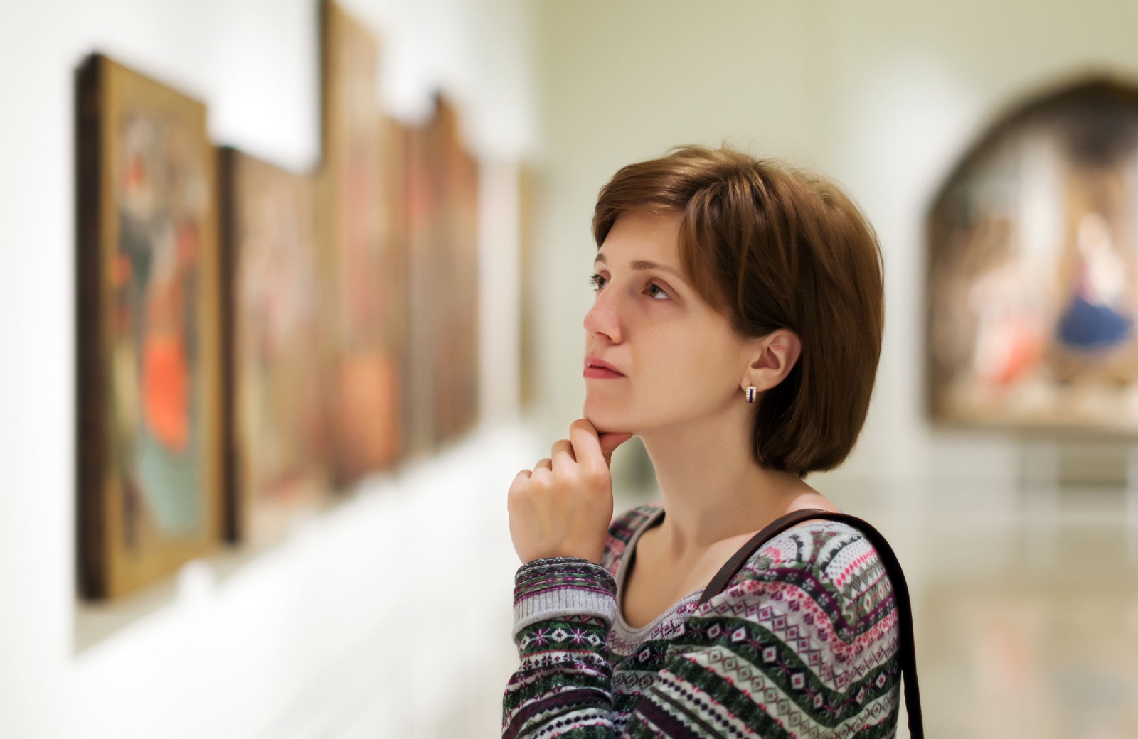 woman with short brown hair looking longingly at a painting in a museum - The Cole NYC East Side apartments