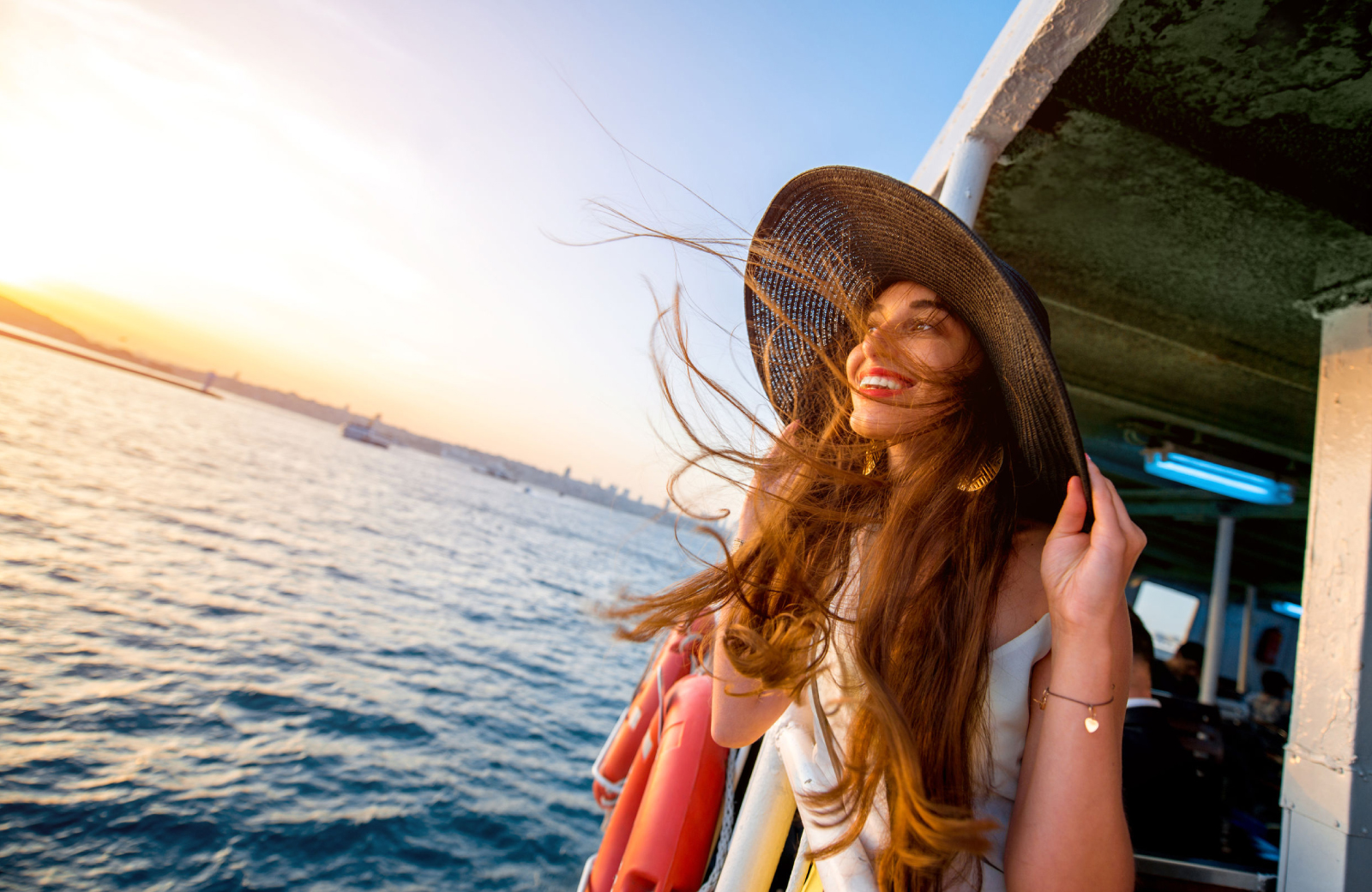 smiling woman with long hair and a large sunhat riding on Sheffield Island Ferry - The Waypointe Apts