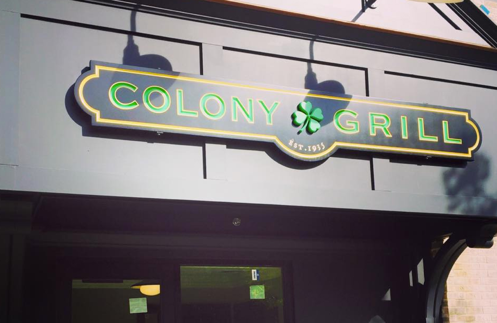 horizontal navy and green Colony Grill restaurant sign with a shamrock in the center - The Waypointe Apts