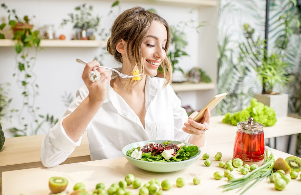 a woman in a white button down shirt eating a salad while looking at her phone - The Madrid westchester ca apartments
