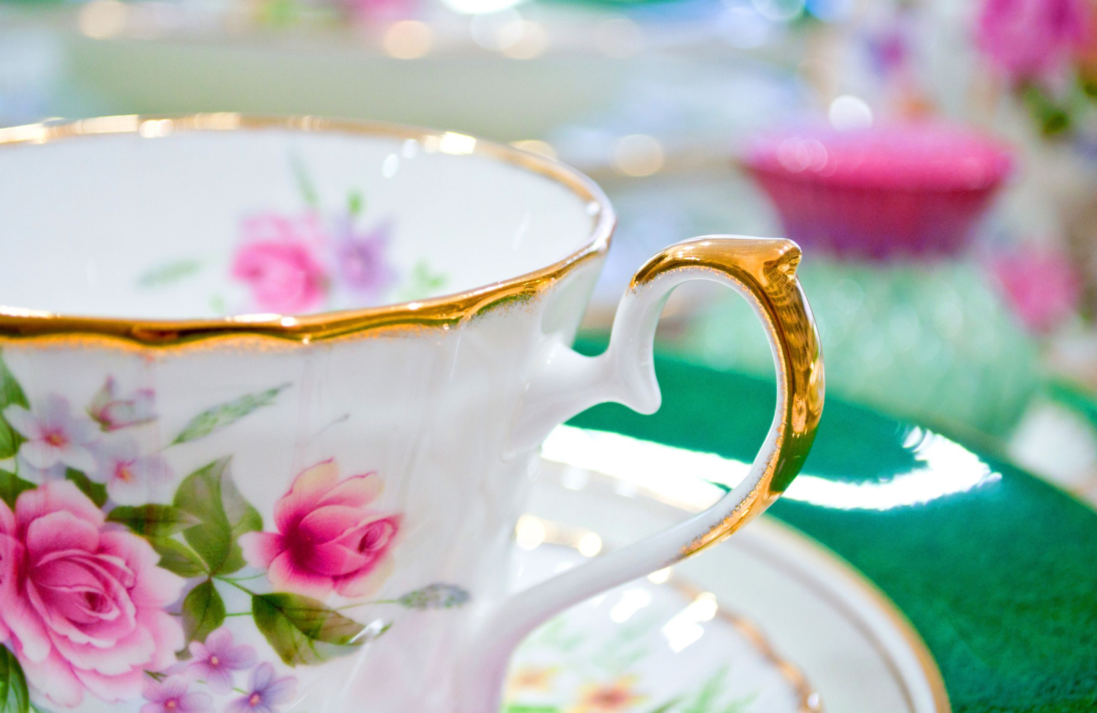 white teacup with pink roses - hosting a tea party - The Vue