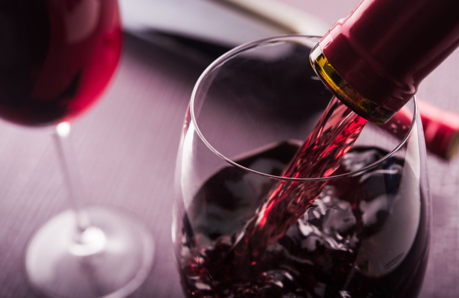 a close up of a bottle of red wine pouring into a wine glass - The Waypointe Apts