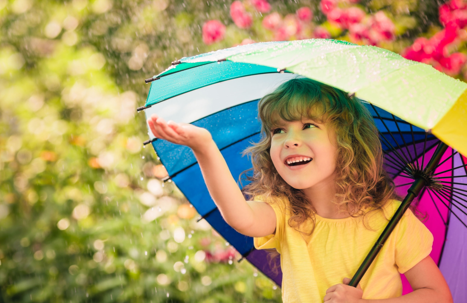 a little girl in a yellow shirt under a rainbow umbrella holding her hand out in the Rain in Norwalk
