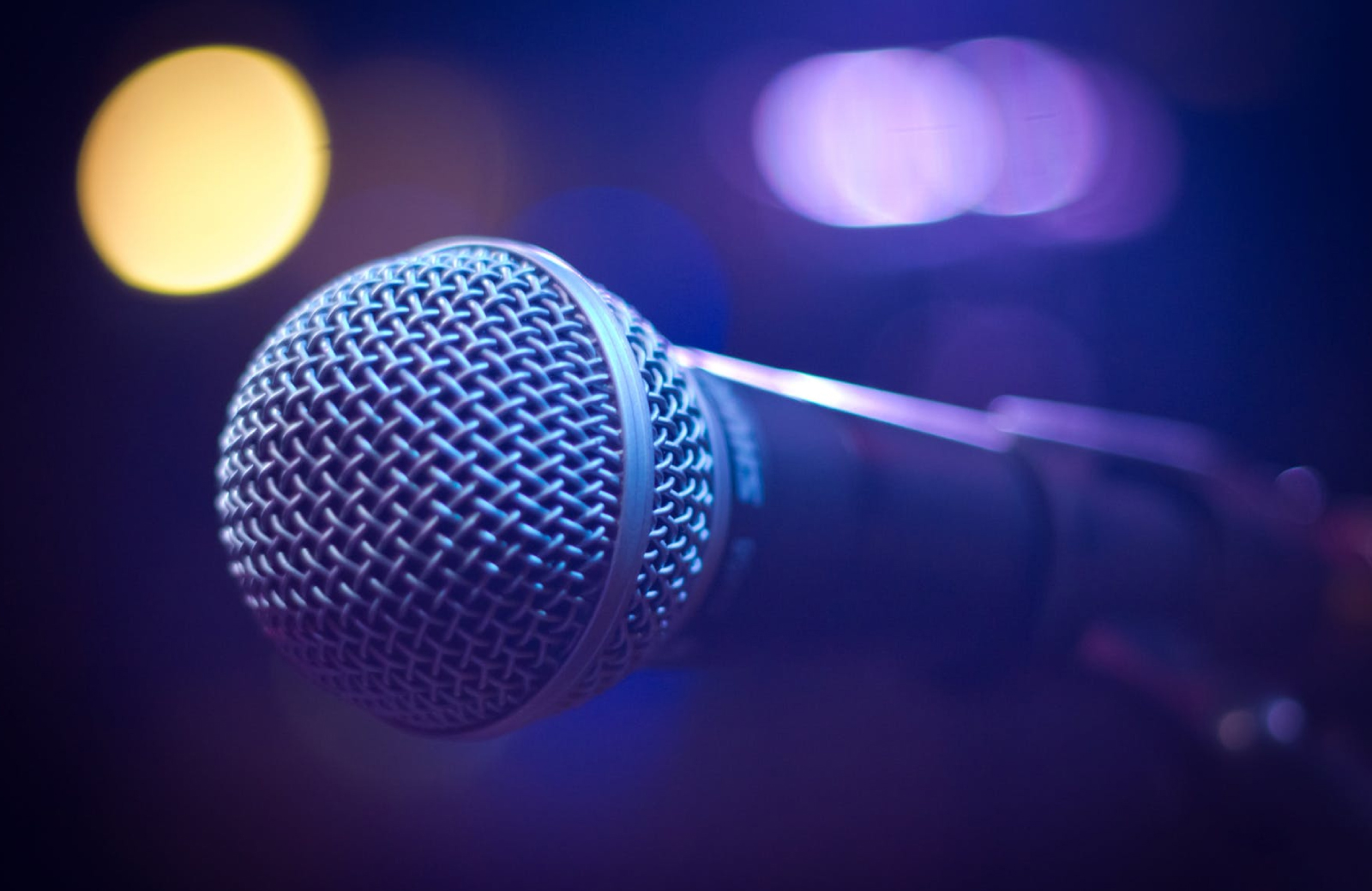 a close up of a karaoke Microphone with blue & yellow lights in the background