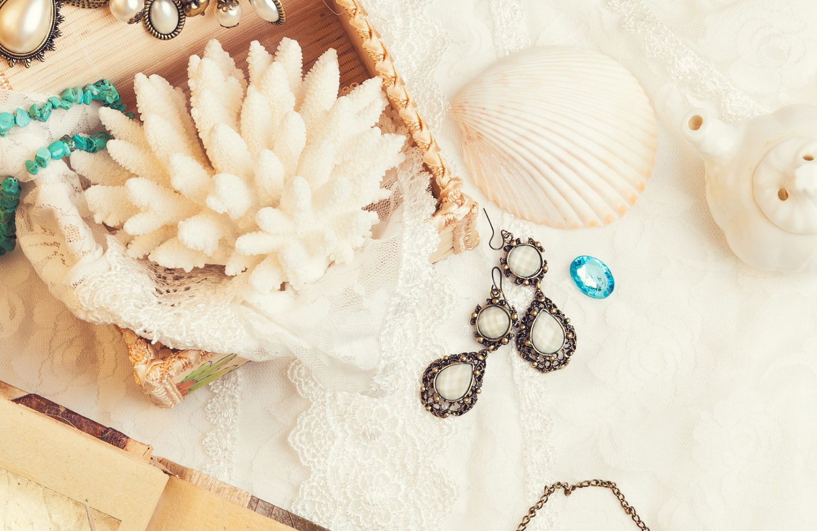 piece of white coral and white seashell on a dresser top with vintage earrings displayed - The Waypointe