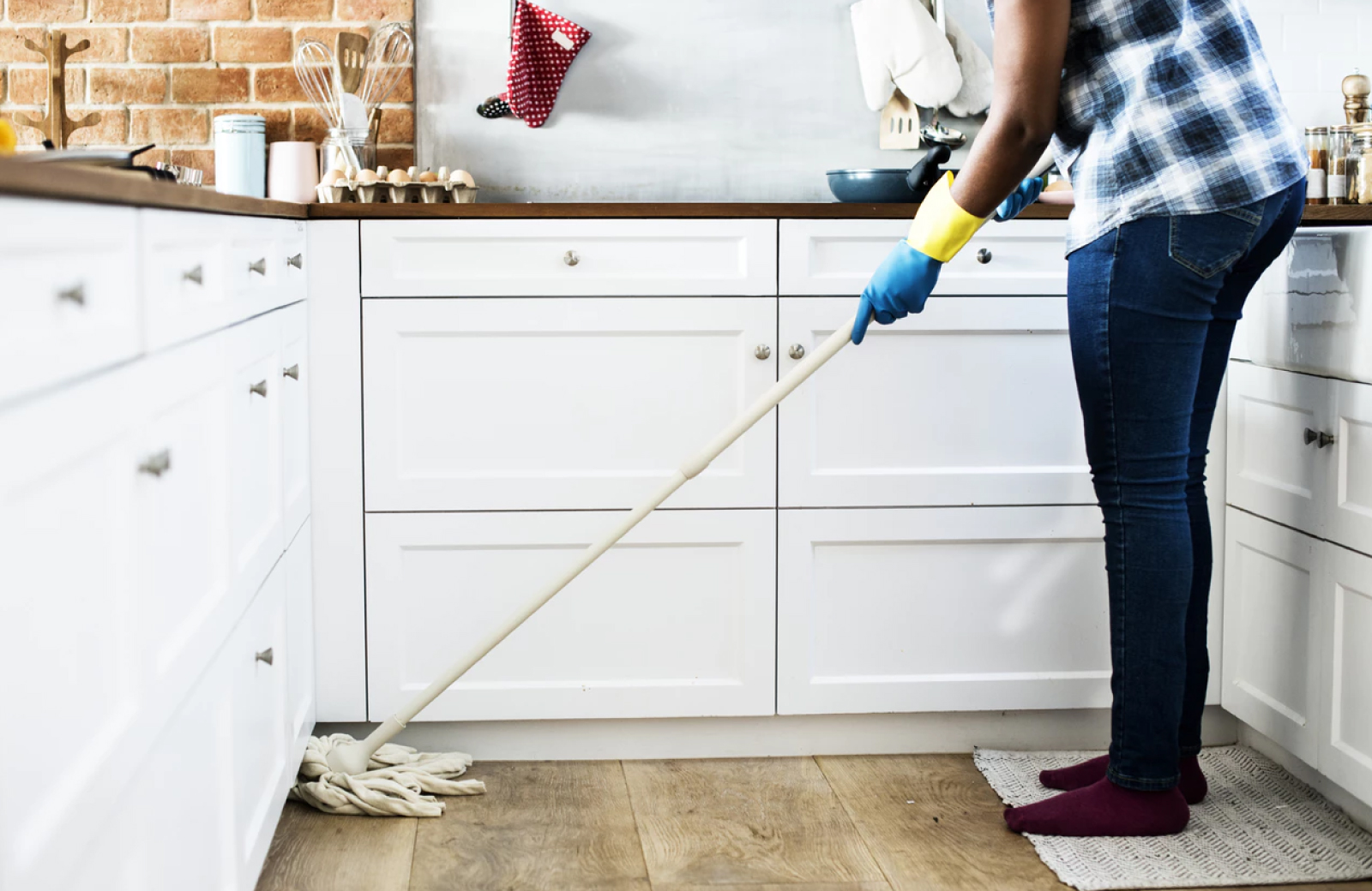 legs of a woman mopping the kitchen floor with green cleaning tools near white cabinets - The Waypointe