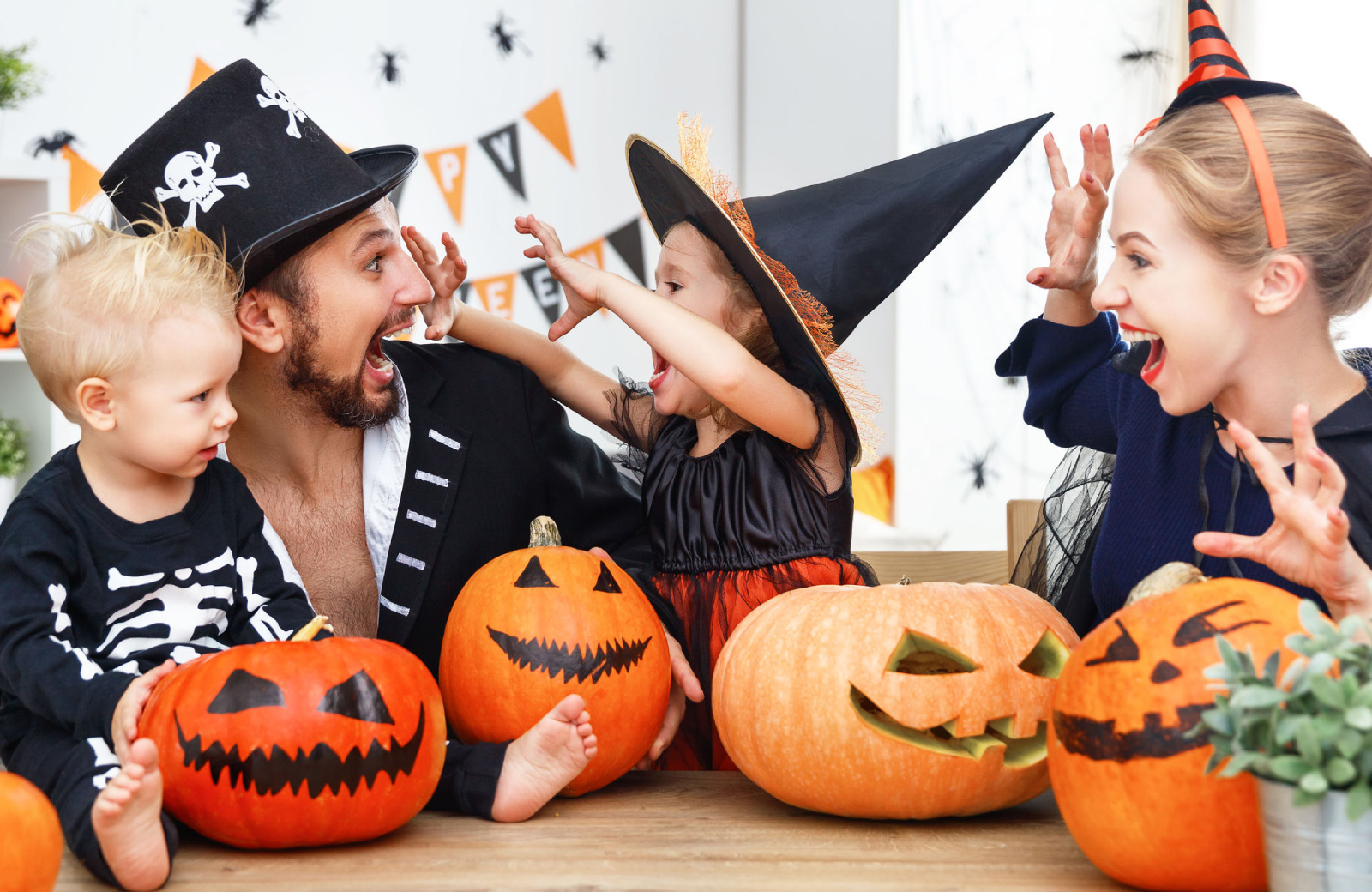 young family with two kids in halloween costumes surrounded by pumpkins waypointe norwalk