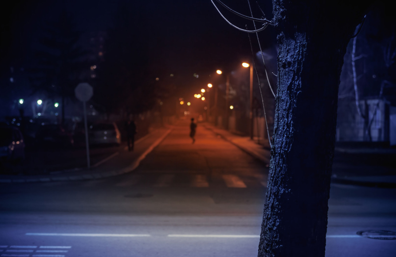 man crossing in a dark street