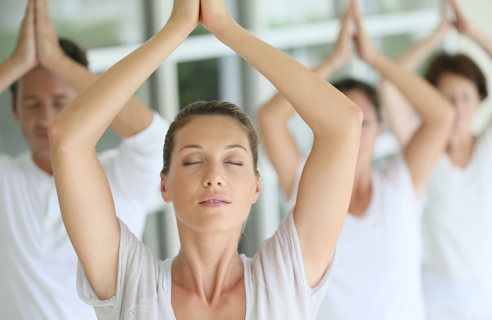 several women in white leotards meditating with arms over their head - 15 cliff ny