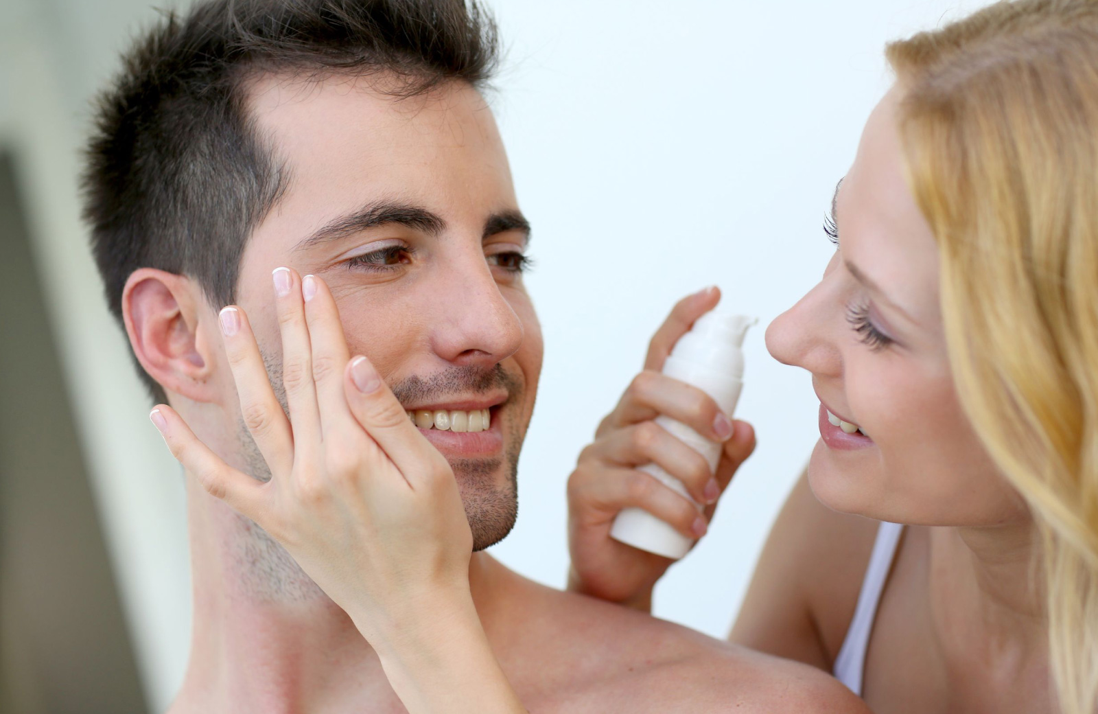 closeup of woman with blonde hair happily applying moisturizer to man with dark hair - Waypointe Apts