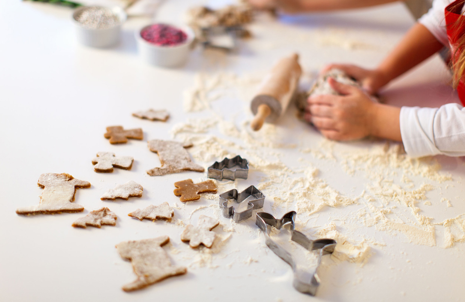 person's hands making holiday cookies with cookie cutters - hyde square bellevue apts