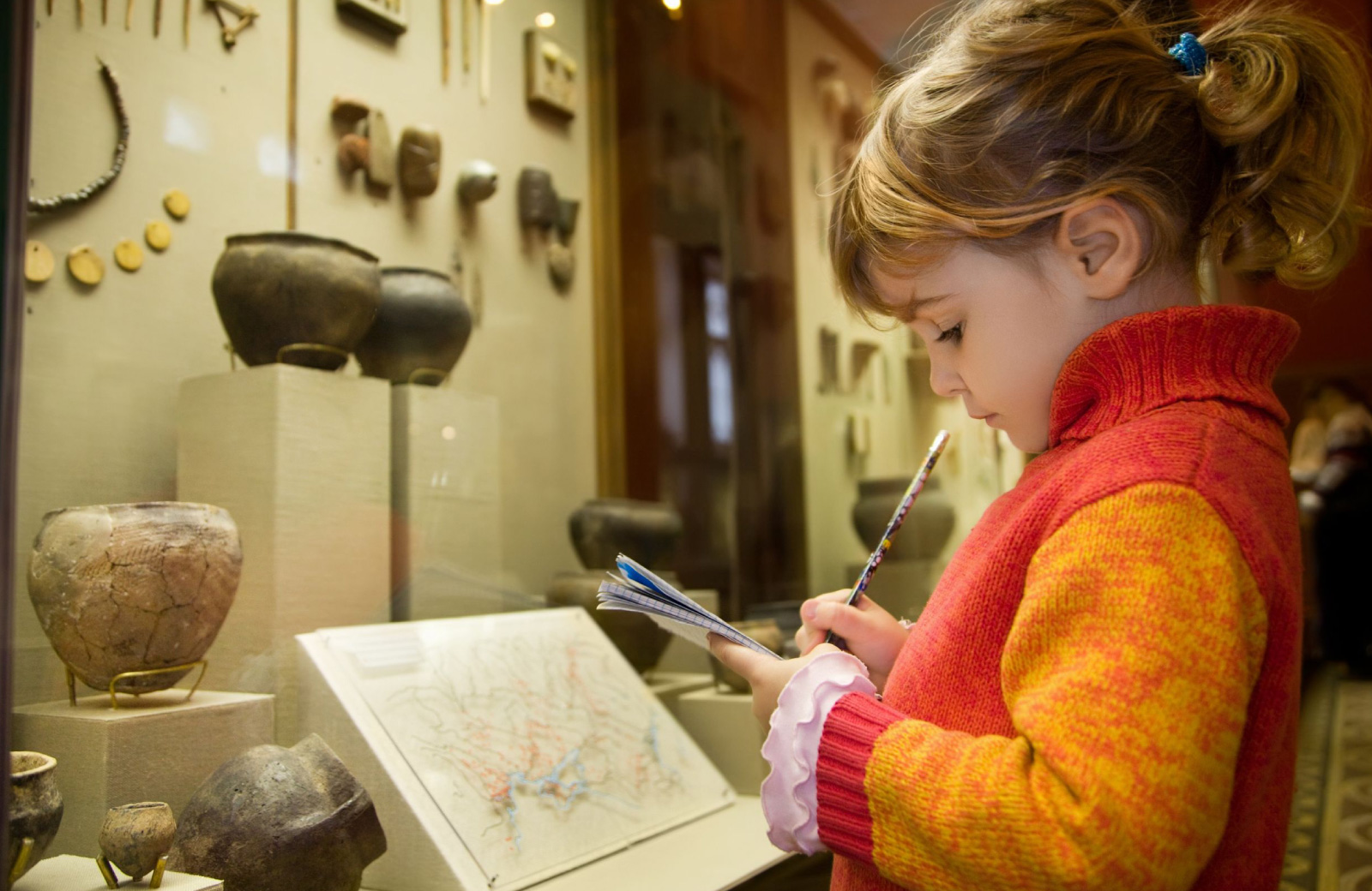 girl taking notes on antique exhibit