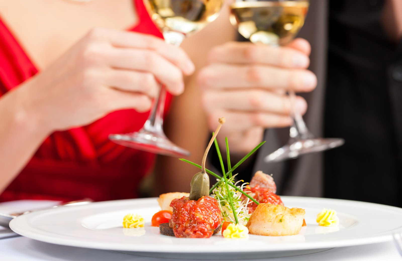 hands of a woman in a red dress eating a tiny plate of food with 2 scallops - The Waypointe