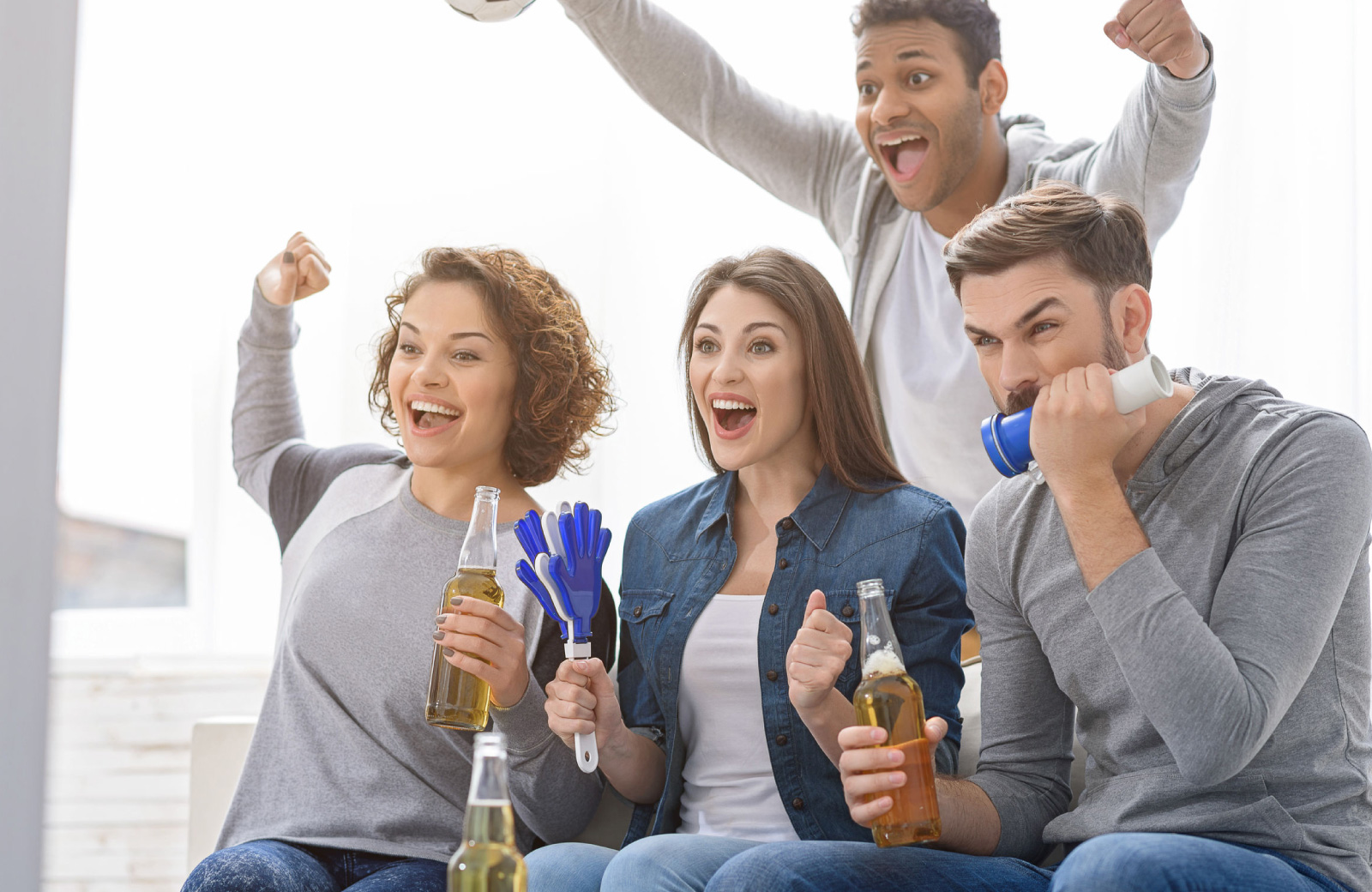 2 guys & 2 girls watching super bowl on tv excitedly - Hyde Square Apts