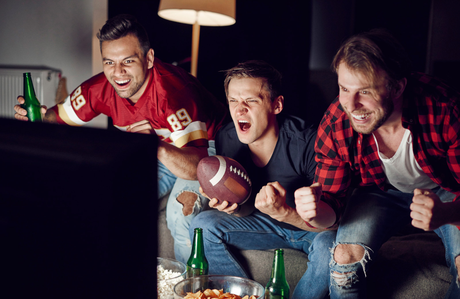 men excitedly watching football on tv