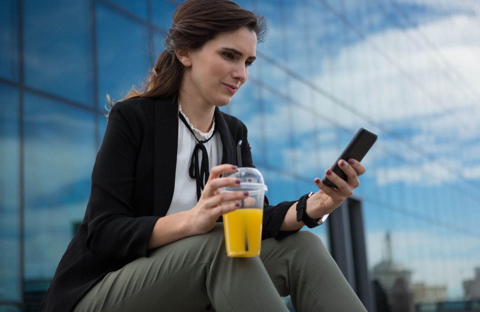 young professional looking woman looking at her phone with drink in hand