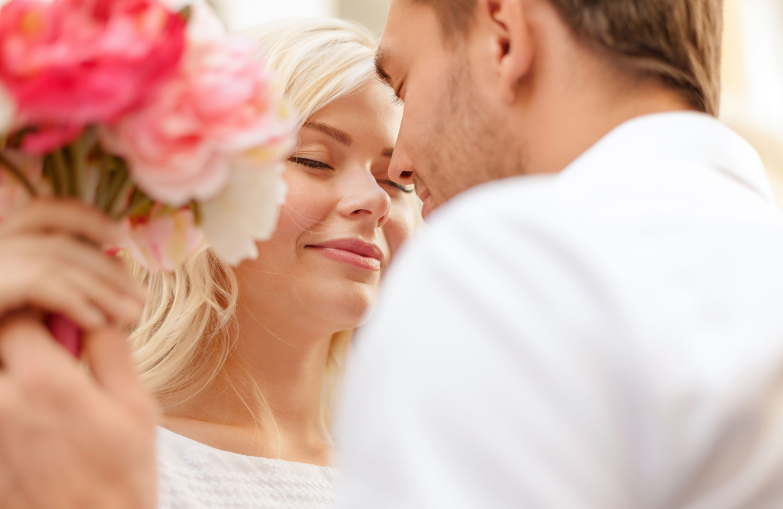 couple about to kiss holding roses - The Waypointe