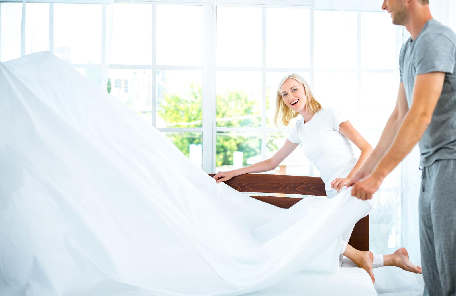 couple unfolding new linen