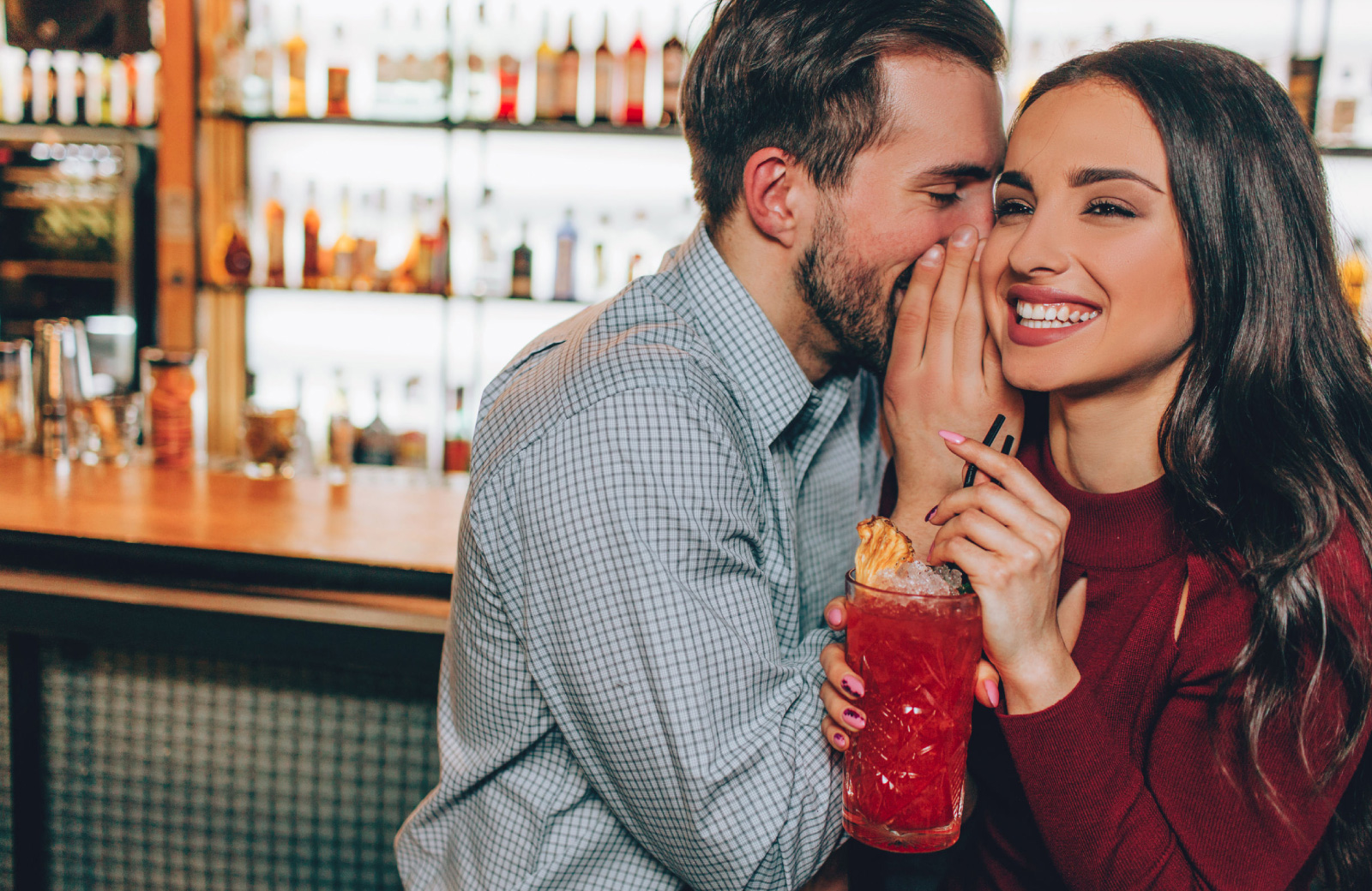 man whispering something to a woman in a bar