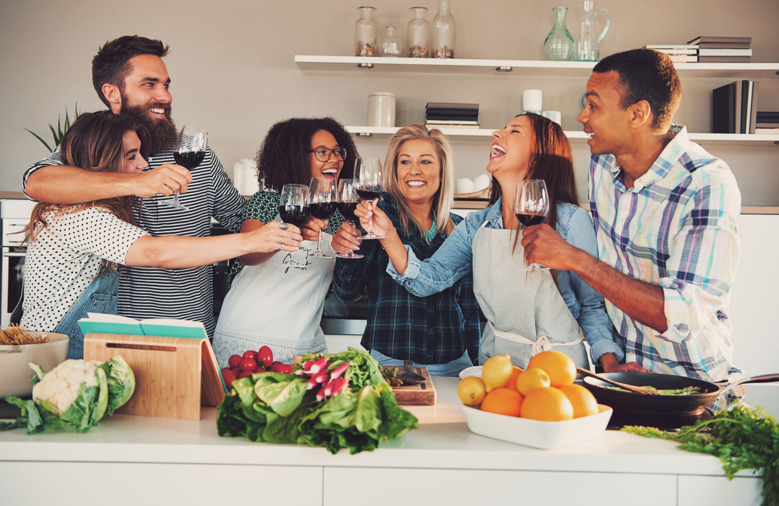 group of friends toasting wine in kitchen