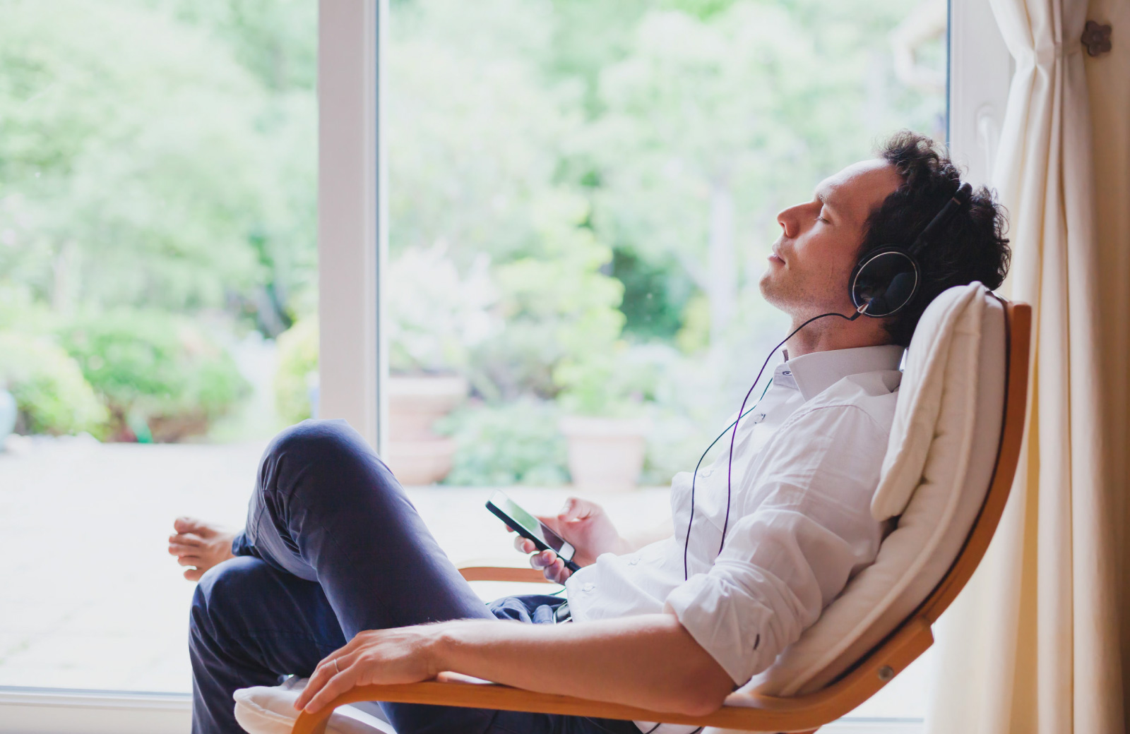man with earphones relaxing on a chair