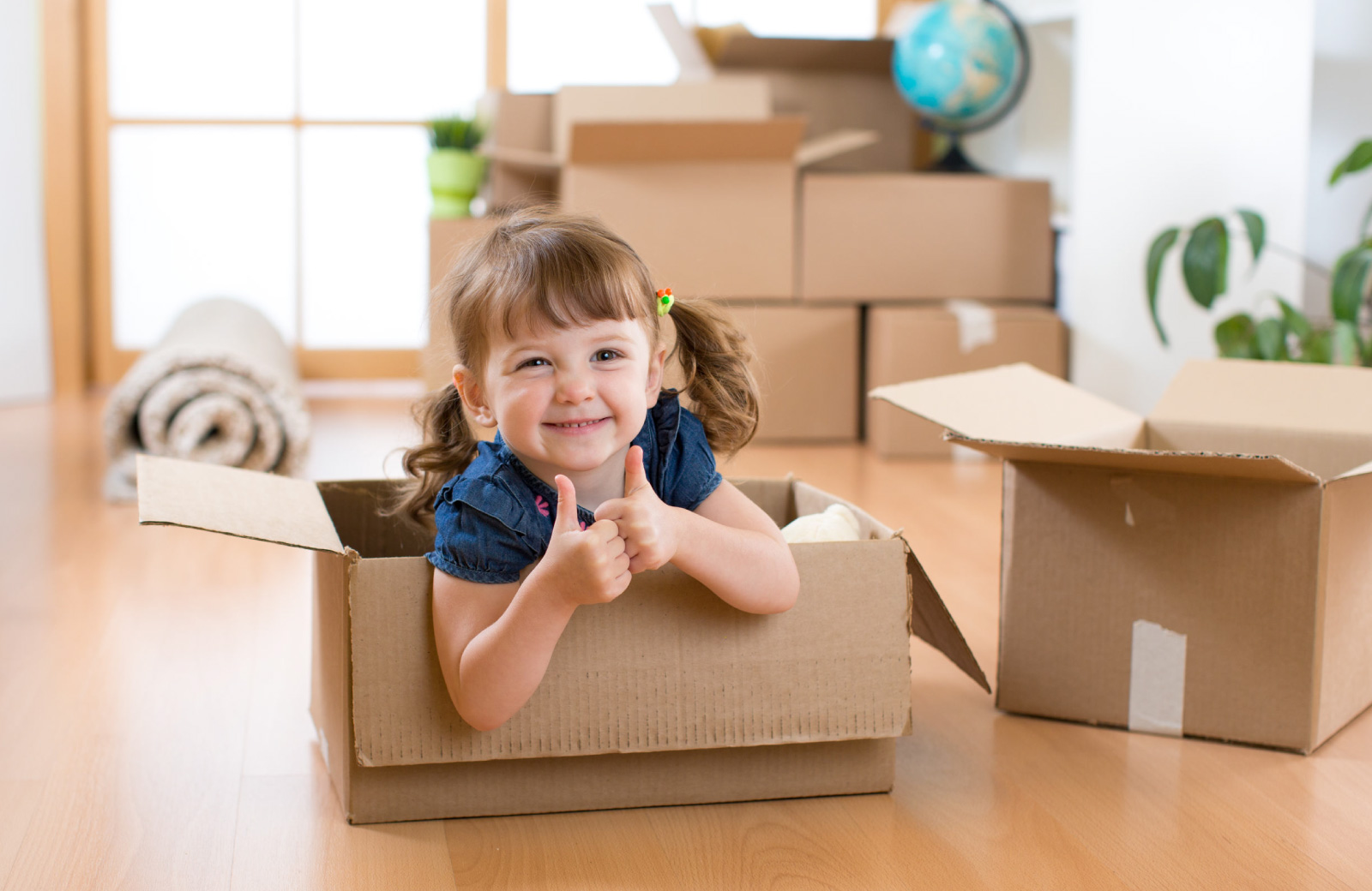 little girl posing and playing with storage boxes