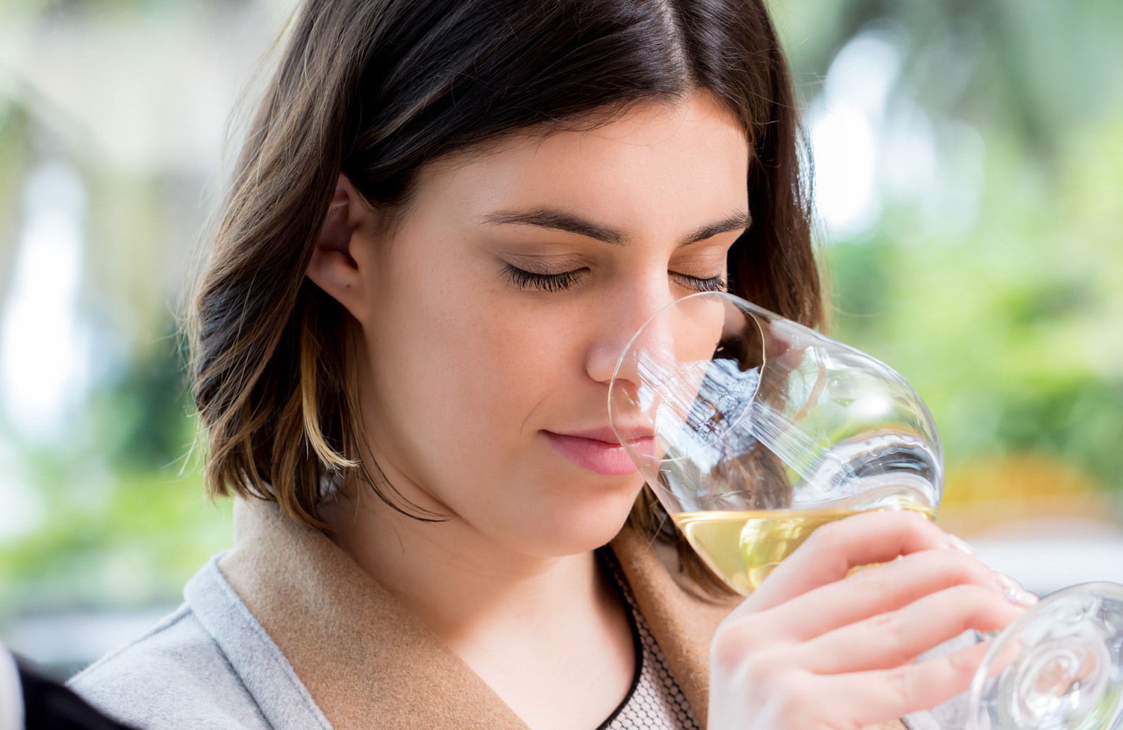 woman smelling white wine