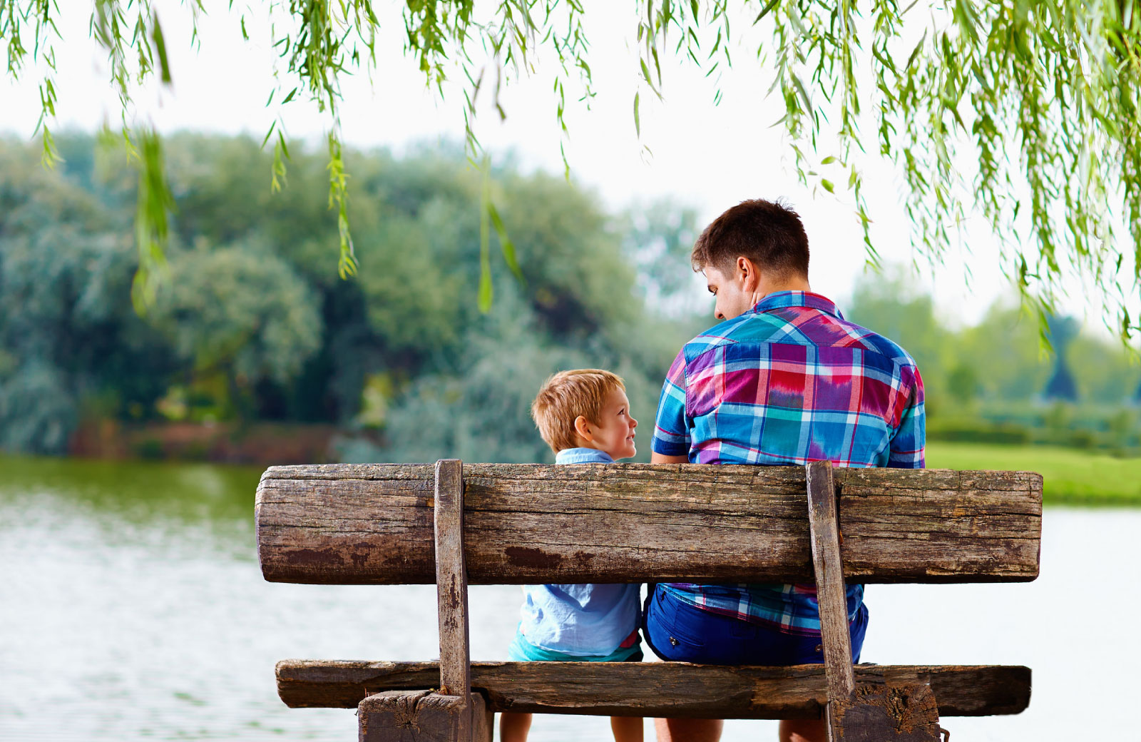 father and son hanging out at the park by the lake