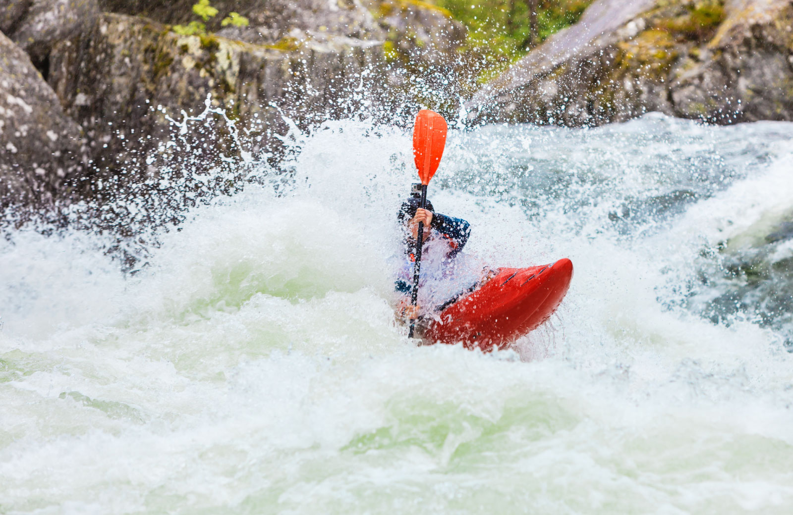 person in a boat whitewater rafting