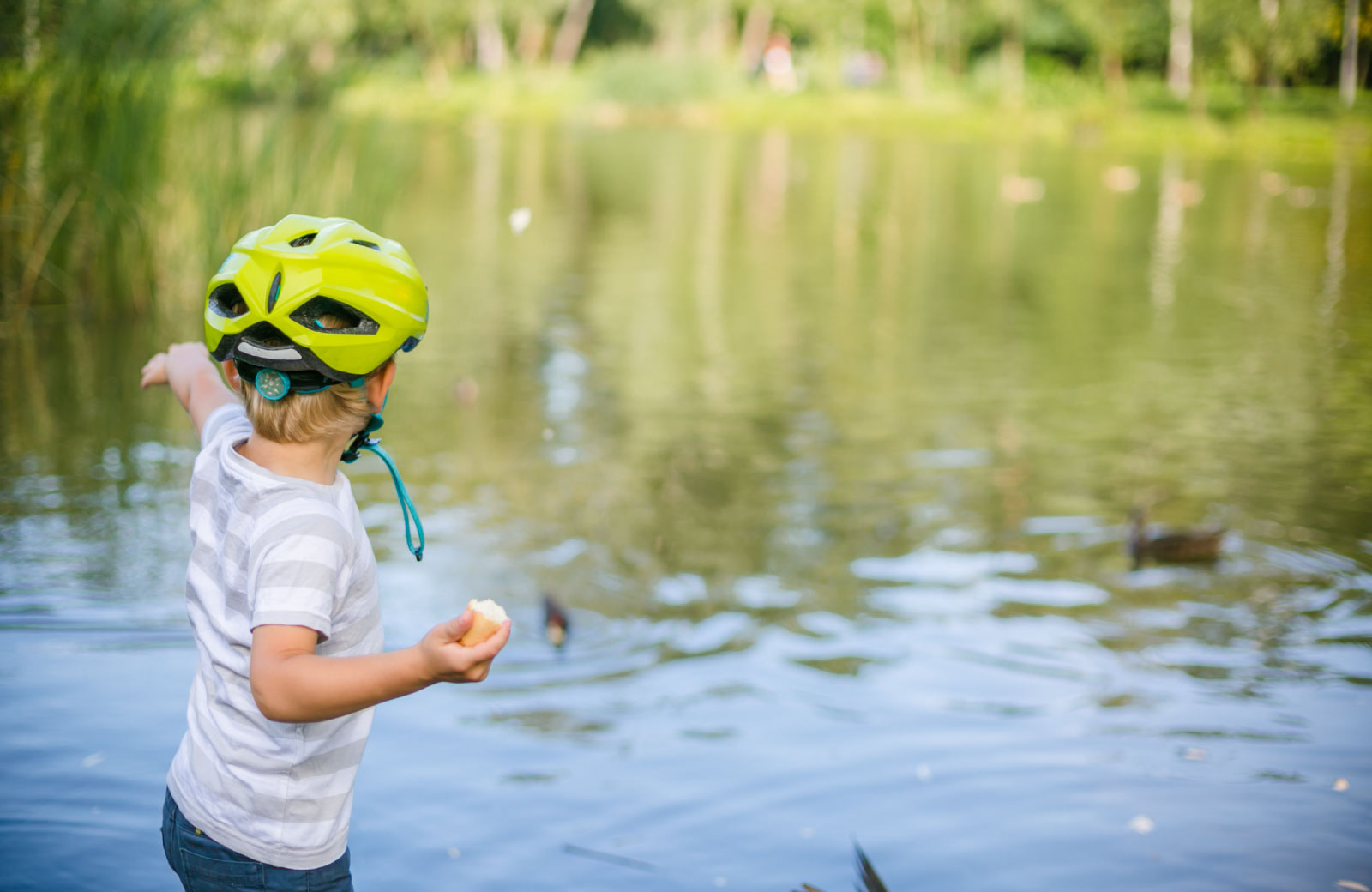child with helmet playing by the lake