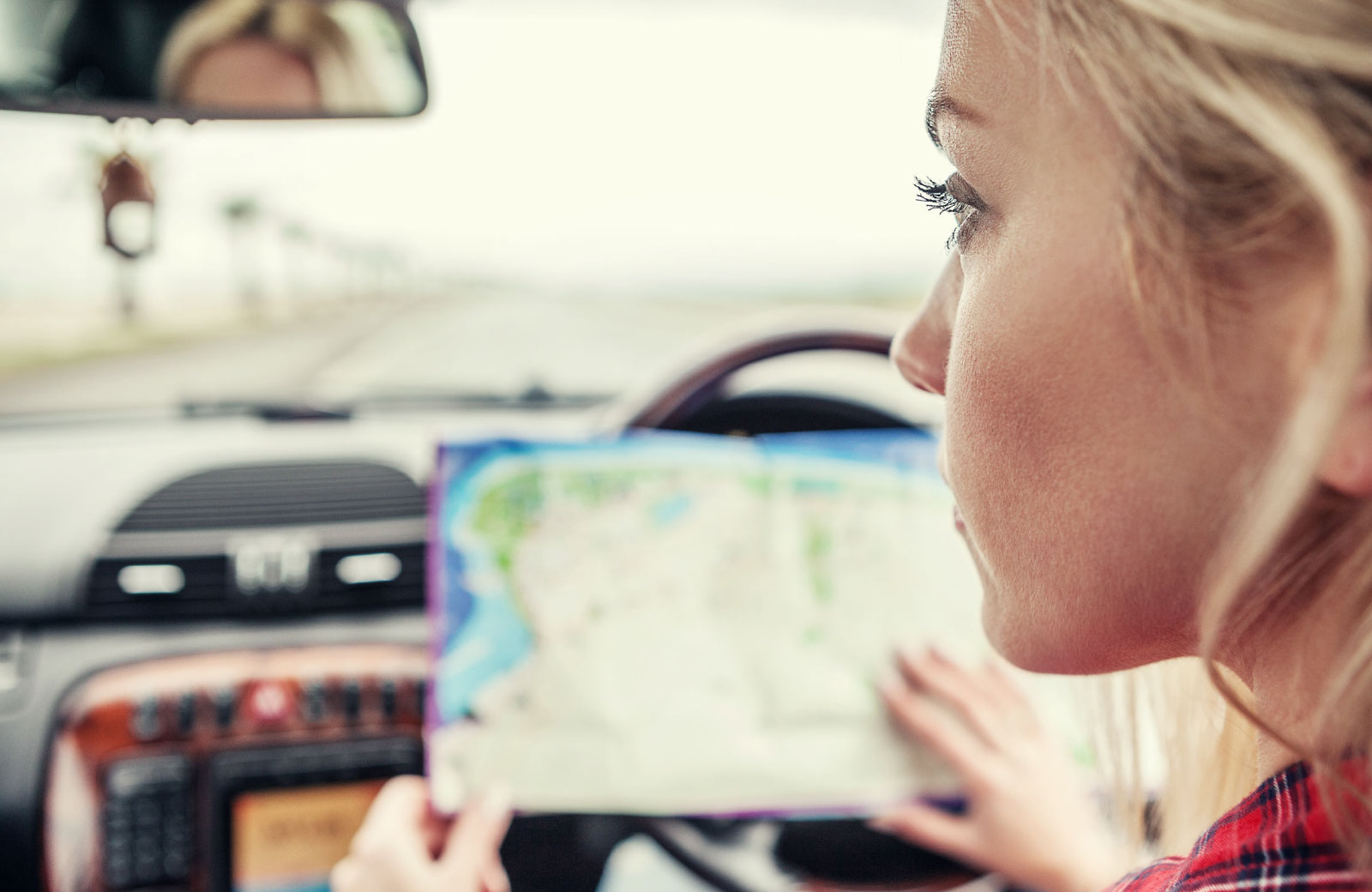 woman looking at a map while on the road
